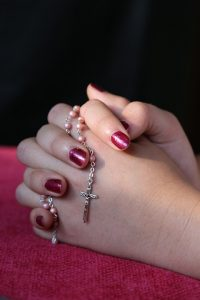 Woman with sexy hands and painted fingernails holds catholic rosary beads